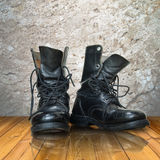 Old black boot on wood floor. Reflect Stock Photo