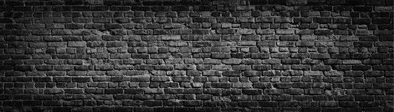 Old black brick wall background. Black brick wall texture, weathered brick surface for panoramic background Royalty Free Stock Photo