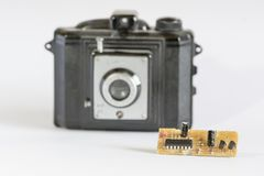 Old black camera and modern electronic component. On white background in a strange combination Royalty Free Stock Photography