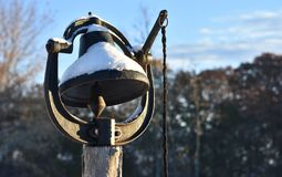 An old black dinner bell with snow on it royalty free stock photo