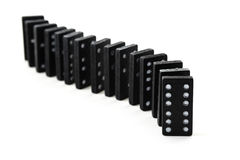 Old black dominos in a row isolated on a white background. Old black dominoes in a row isolated on a white background, selective focus and narrow depth of field Stock Photo