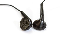 Old black earphones on a white Royalty Free Stock Images