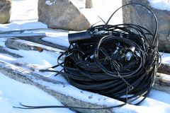 Old black electric wire. Black electric wire on the ground on winter Stock Image