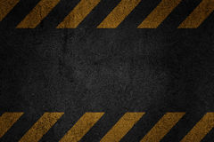 Old black grungy asfalt surface with yellow warning stripes Stock Photos