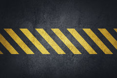 Old black grungy metal plate surface with yellow warning stripes Royalty Free Stock Photos