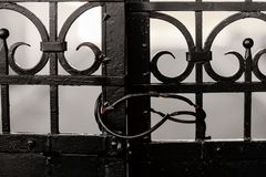 Old Black Iron Gate Closed Locked. Old Black Iron Gate closed with some buildings in the background royalty free stock photos