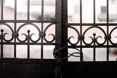 Old Black Iron Gate Closed Locked. Old Black Iron Gate closed with some buildings in the background stock image