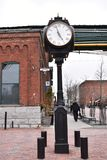 Old black iron hall clock at the Distillery District and many red buildings in Toronto, Canada. Beautiful old black iron hall clock at the Distillery District royalty free stock photography