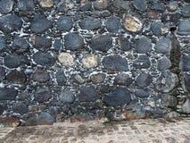 Old black irregular patterned stone wall Stock Photo