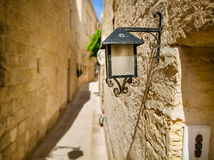 Old black lantern on the stone wall. Stock Image