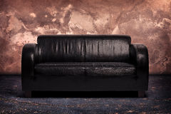 Old black leather couch. Old leather lounge couch on wooden floor with sandstone background Royalty Free Stock Photo