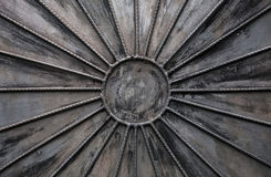 Old black metal wall with sun shaped decoration Royalty Free Stock Photo