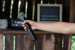 Old black microphone in hand. Royalty Free Stock Photo