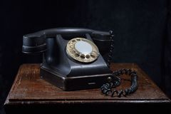 An old, black phone. Close-up. On an old, wooden table stock photo
