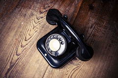 Old black phone with dust and scratches on wooden floor Stock Images