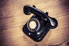 Old black phone with dust and scratches on wooden floor Stock Photography