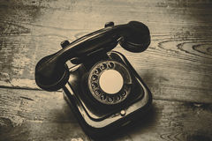 Old black phone with dust and scratches on wooden floor Royalty Free Stock Image