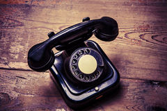 Old black phone with dust and scratches on wooden floor Royalty Free Stock Photo