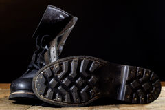 Old black Polish military boots on a wooden table. Royalty Free Stock Image