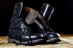 Old black Polish military boots on a wooden table. Royalty Free Stock Photo