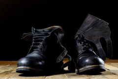 Old black Polish military boots on a wooden table. Stock Images