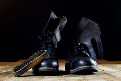 Old black Polish military boots on a wooden table. Royalty Free Stock Photography