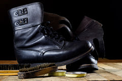 Old black Polish military boots on a wooden table. Stock Photography