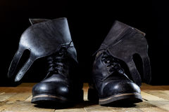 Old black Polish military boots on a wooden table. Stock Photos