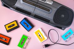 Old black retro cassette music audio tape recorder and retro cassette tape collection. On pink background stock photos