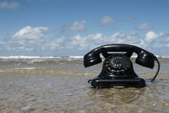 Retro Phone in the Water. Old black retro Phone on the Beach Stock Photography