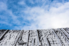 The old black roof with white snow on a background cloudy sky. Royalty Free Stock Images