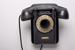 Old black rotational phone. On wall Royalty Free Stock Photography