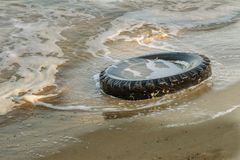 Old black rubber tire left on beach, environment pollution concept, selective focus, color toned picture. Discarded old tyre in bl. Ue water on beach. Pollutions royalty free stock image