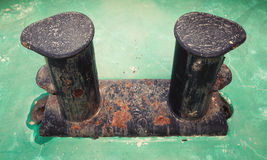 Old black rusted bollard on green ship deck Royalty Free Stock Image