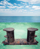 Old black rusted stern bollard mounted on green ship deck Stock Photos
