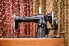 The old black sewing machine. Old black sewing machine white spool of thread on the background of blinds Stock Photos