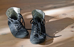 Old black sneakers. Old black worn out sneakers on wooden floor Royalty Free Stock Photography