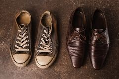 Old black sneakers and brown classic shoes on a dark marble background. Stock Photo