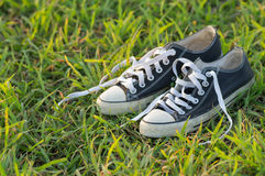 Old black sneakers on the grass at daytime. Outdoors Royalty Free Stock Images