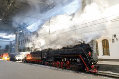 Old black steam locomotive in Russia in the winter on the background of the Moscow railway station Stock Image