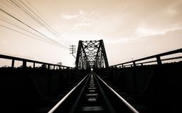 Old black steel train bridge Lampang Thailand to Chiangmai Thail. And in the evening with blue sky cloud and sun, Black White Picture Royalty Free Stock Photography