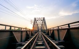 Old black steel train bridge Lampang Thailand to Chiangmai Thail. And in the evening with blue sky cloud and sun Royalty Free Stock Photography