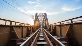 Old black steel train bridge Lampang Thailand to Chiangmai Thail. And in the evening with blue sky cloud and sun Royalty Free Stock Image