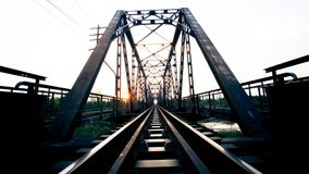 Old black steel train bridge Lampang Thailand to Chiangmai Thail. And in the evening with blue sky cloud and sun Stock Photography