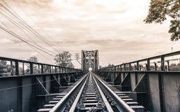 Old black steel train bridge Lampang to Chiangmai, blue sky clou. D and trees Stock Photo