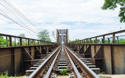 Old black steel train bridge Lampang to Chiangmai, blue sky clou. D and trees Stock Images