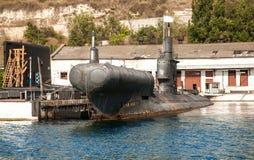 Old black submarine in docks. Old black submarine standing in docks royalty free stock photos