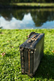 Old black suitcase by the river Stock Photography