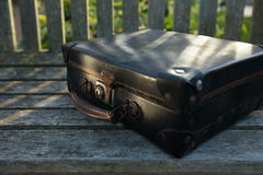 Old black suitcase on wooden bench Stock Photos