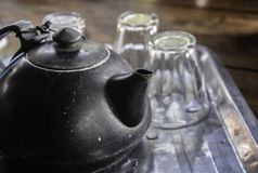 Old black teapot with three clear glass cups Set on stainless steel tray royalty free stock photo